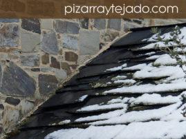 Encuentro de pared de piedra y tejado de pizarra natural.