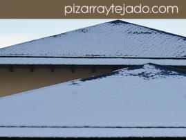 Nieve sobre tejados de pizarra sin canalones.