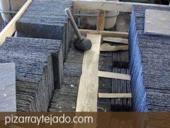 Detalle de operación de llenado de pallet de pizarra para tejados.