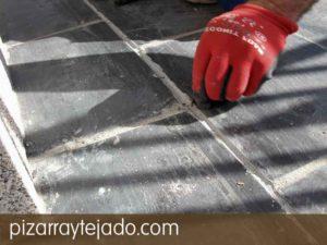 Detalle de limpieza manual de junta de dilatación en suelo de plaqueta de pizarra para suelos exteriores.