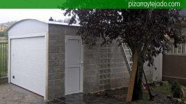 Vista exterior de obra de cochera con dos puertas de acceso. Reparación tejados Bierzo.