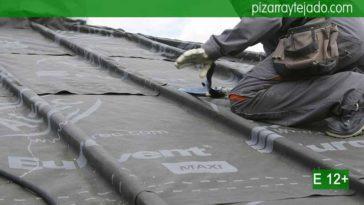 Colocación de membrana impermeable y transpirable sobre rastrel de madera de castaño en cubierta de pizarra natural.